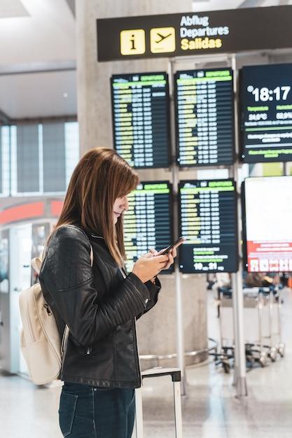 Jeune femme attend et vérifie son vol à l'aéroport avec son téléphone portable. notion de voyage et de vacances. Photo Premium