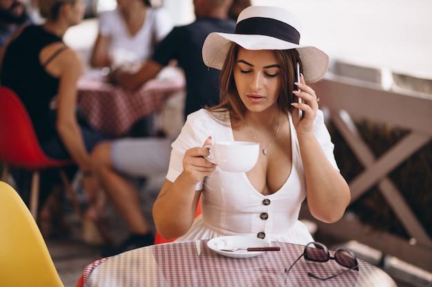 Jeune femme au bar, boire du café et parler au téléphone Photo gratuit