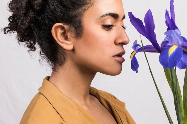Jeune femme au bouquet de fleurs d'iris bleu Photo gratuit