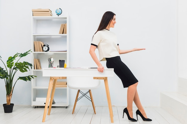 Jeune femme au bureau tenant quelque chose sur la paume Photo gratuit