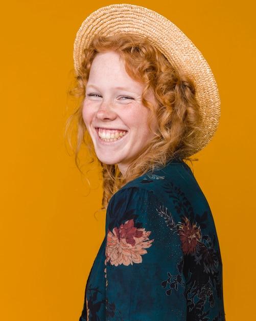 Jeune femme au chapeau et aux cheveux bouclés souriant Photo gratuit