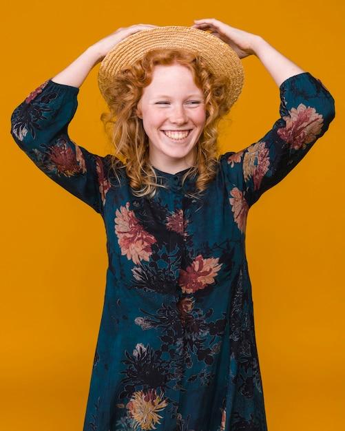 Jeune femme au chapeau avec des cheveux bouclé roux souriant Photo gratuit