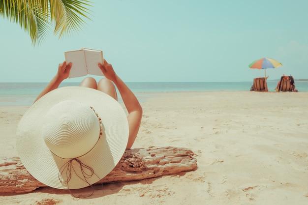 Jeune femme au chapeau de paille se trouvant bronzer sur une plage tropicale Photo Premium