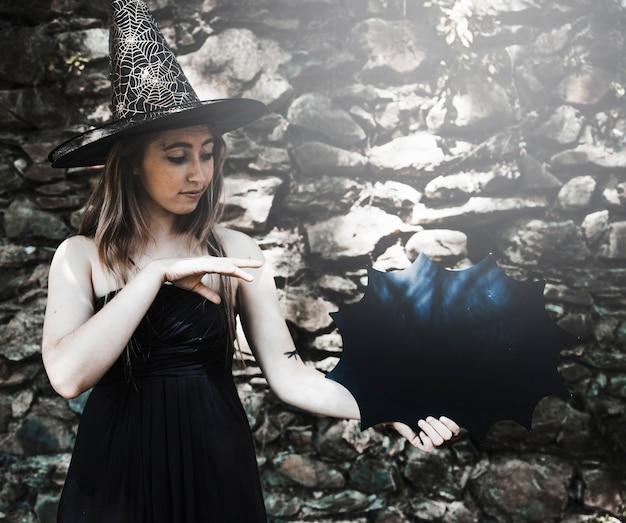 Jeune femme au chapeau de sorcière montrant la magie avec la décoration de halloween Photo gratuit