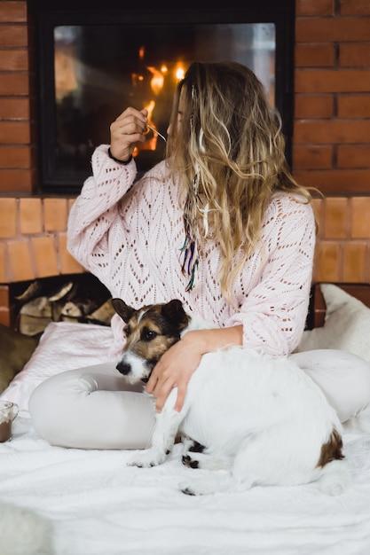 Jeune femme au coin du feu boit du cacao à la guimauve avec un chien. Photo Premium