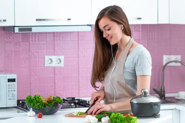 Jeune Femme Au Foyer Dans Un Casque Et Dans Un Tablier En écoutant De La Musique Et En Appréciant La Préparation De La Cuisine Dans La Cuisine à La Maison. Aime Cuisiner Photo Premium