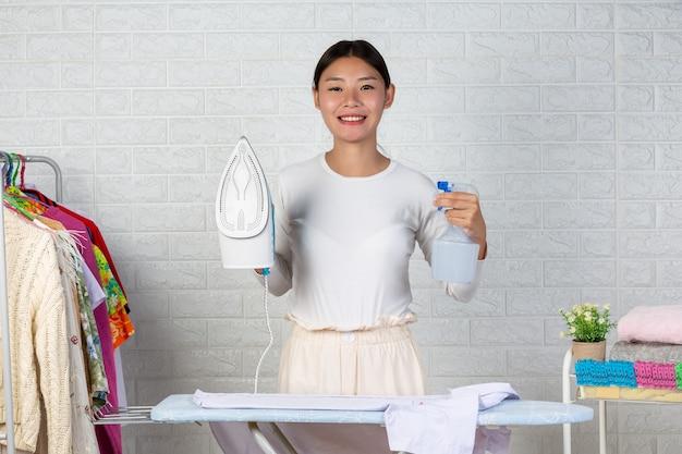 La jeune femme au foyer qui se contente de son fer sur une brique blanche. Photo gratuit
