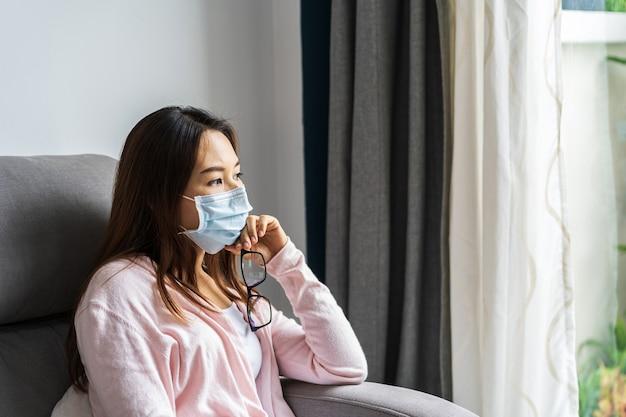 Jeune Femme Au Masque Médical Assis Sur Un Canapé Photo Premium