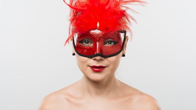 Jeune femme au masque avec des plumes rouges Photo gratuit