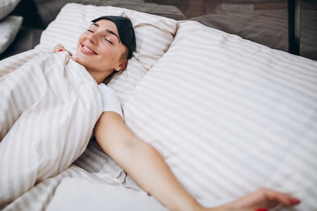 Jeune femme au repos au lit le matin Photo gratuit