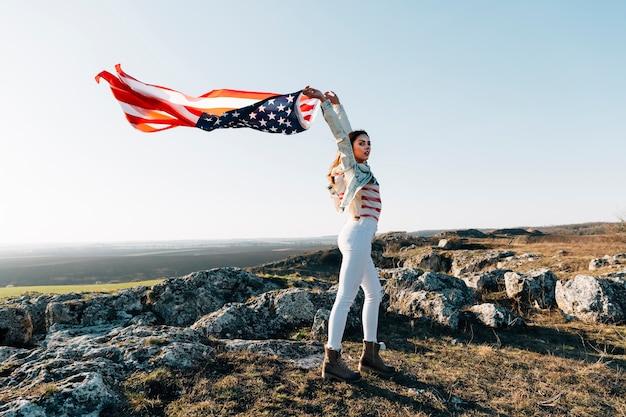 Jeune femme au sommet de la montagne avec drapeau américain flottant Photo gratuit