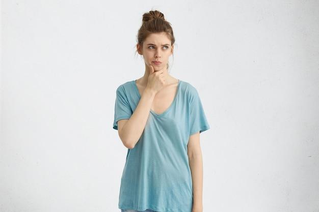 Jeune Femme Au Visage Ovale, Yeux Bleus Attrayants Ayant Ses Cheveux Attachés En Noeud Habillé En Chemise Ample Tenant La Main Sur Le Menton à La Recherche Avec Une Expression Rêveuse Fronçant Les Sourcils En Pensant à Quelque Chose Photo gratuit