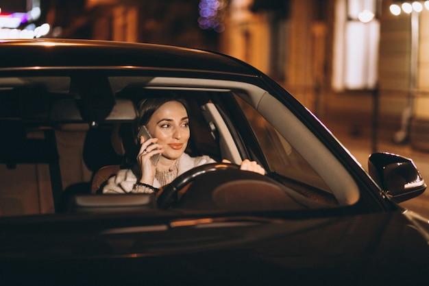 Jeune femme au volant de voiture la nuit Photo gratuit