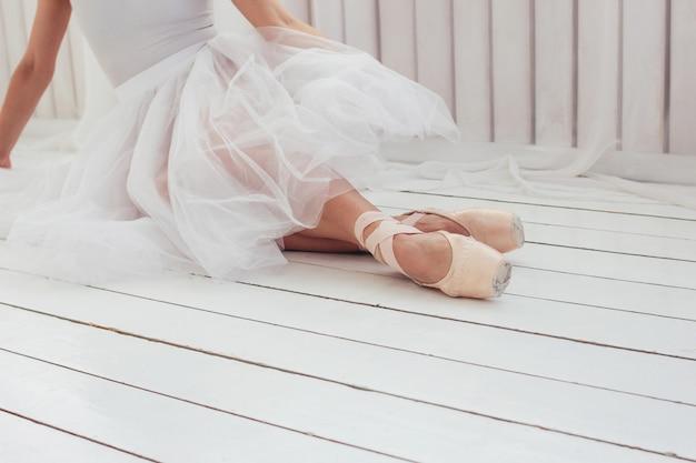Jeune femme authentique ballerine danseuse classique en pointe shous assise sur le sol blanc Photo Premium