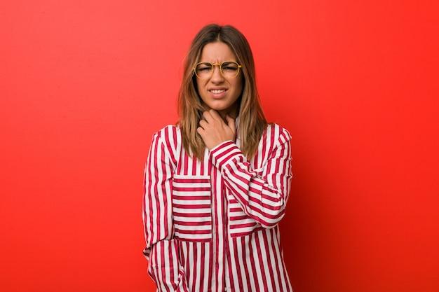Jeune femme authentique, charismatique et réelle, une femme contre un mur a mal à la gorge à cause d'un virus ou d'une infection. Photo Premium