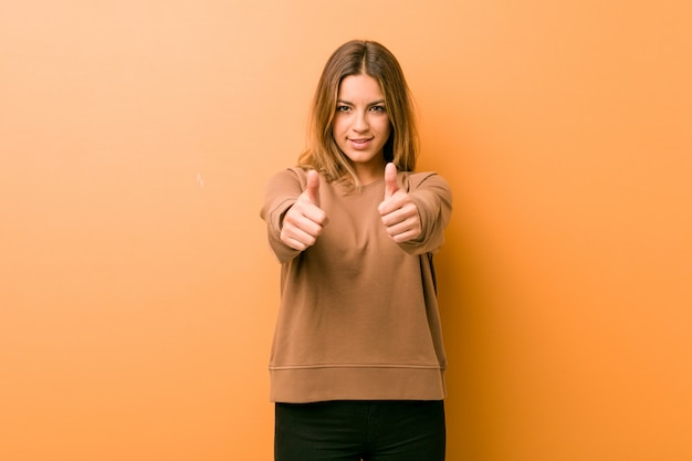 Jeune femme authentique, de vraies personnes charismatiques, adossée à un mur, acclamant quelque chose, soutien et respect. Photo Premium