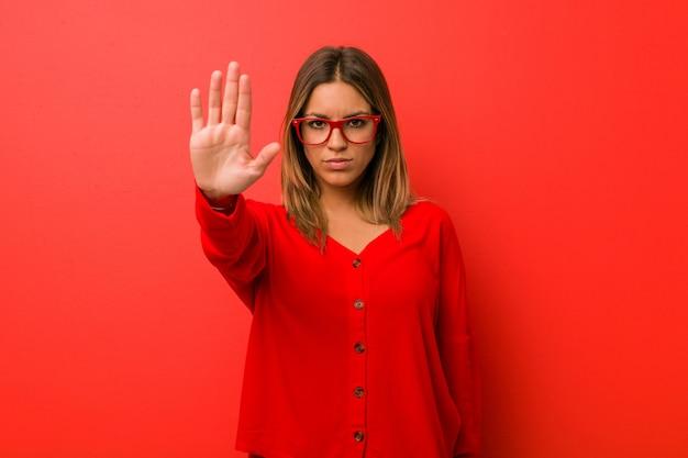 Jeune femme authentique de vraies personnes charismatiques contre un mur debout avec la main tendue montrant un panneau d'arrêt vous empêchant. Photo Premium