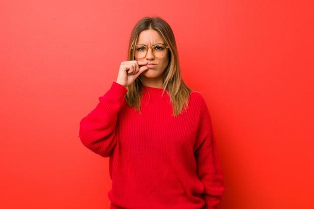 Jeune femme authentique de vraies personnes charismatiques contre un mur avec les doigts sur les lèvres, gardant un secret. Photo Premium