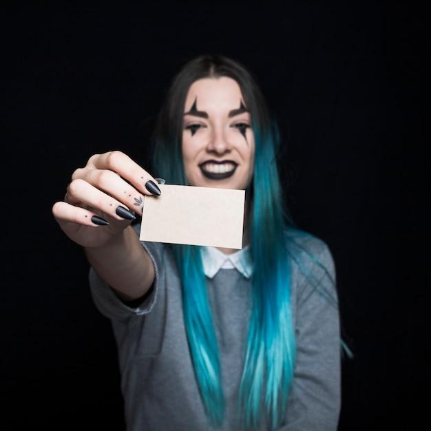 Jeune femme aux cheveux bleue posant avec une carte de papier Photo gratuit