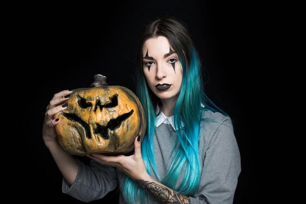 Jeune femme aux cheveux bleue posant avec citrouille Photo gratuit