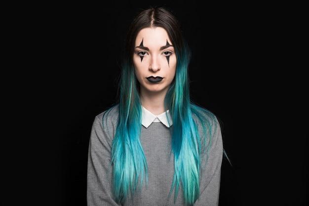 Jeune femme aux cheveux bleus et maquillage debout en studio Photo gratuit