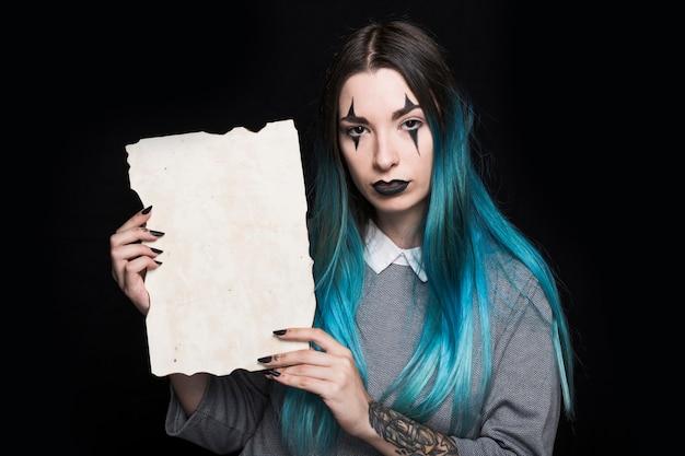 Jeune femme aux cheveux bleus posant avec une feuille de papier Photo gratuit