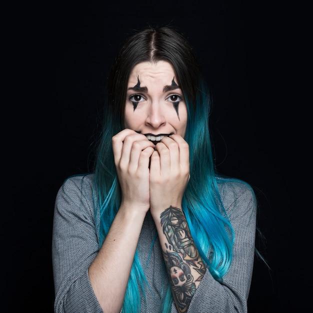 Jeune femme aux cheveux bleus et visage effrayé qui pose en studio Photo gratuit