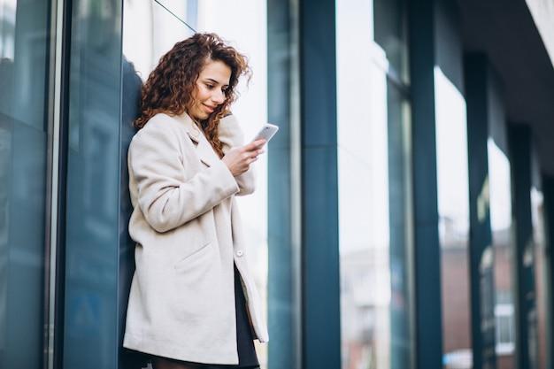 Jeune femme aux cheveux bouclés à l'aide de téléphone à la rue Photo gratuit