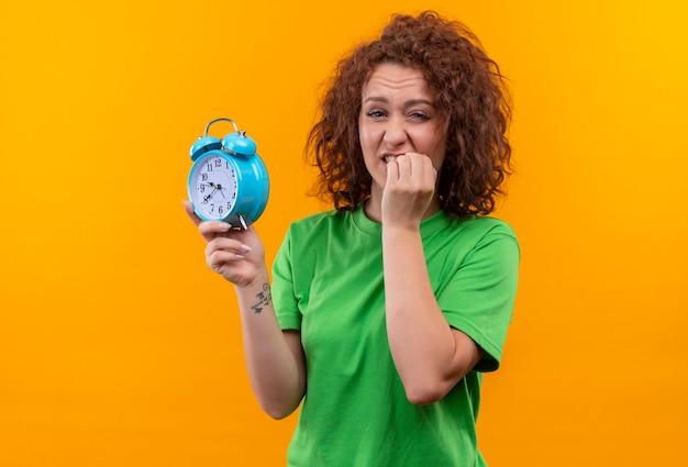 Jeune Femme Aux Cheveux Bouclés Courts En T-shirt Vert Tenant Un Réveil A Souligné Et Nerveux Mordant Les Ongles Debout Sur Le Mur Orange Photo gratuit