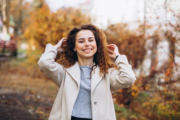 Jeune femme aux cheveux bouclés dans le parc Photo gratuit