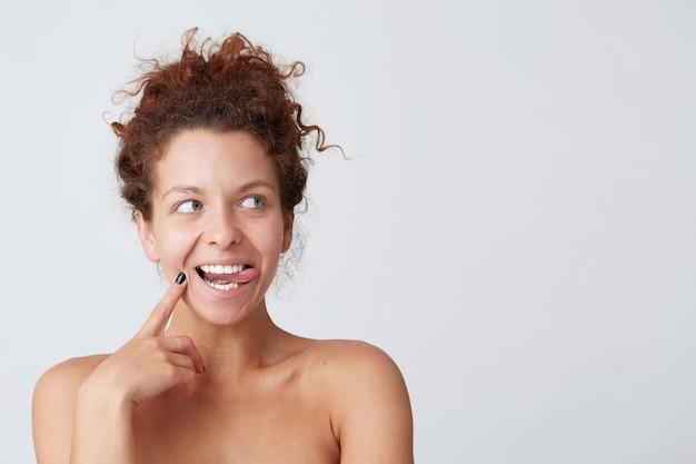 Jeune Femme Aux Cheveux Bouclés Rouges Posant Et Faisant La Grimace Photo gratuit