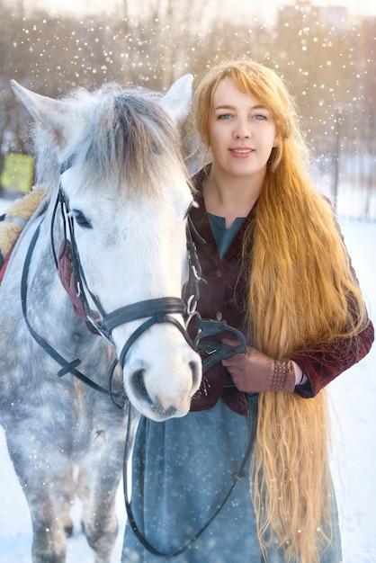 Jeune femme aux cheveux longs à cheval en hiver Photo Premium