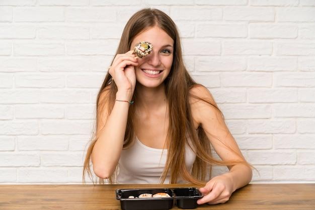 Jeune femme aux cheveux longs mangeant des sushis Photo Premium