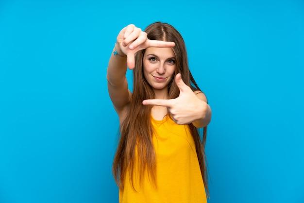 Jeune femme aux cheveux longs sur le mur bleu isolé, se concentrant sur le visage. symbole d'encadrement Photo Premium