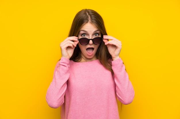 Jeune femme aux cheveux longs sur un mur jaune isolé avec des lunettes et surpris Photo Premium