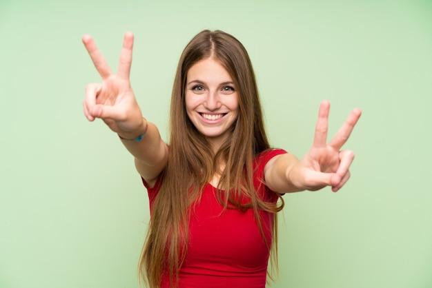 Jeune femme aux cheveux longs sur un mur vert isolé, souriant et montrant le signe de la victoire Photo Premium