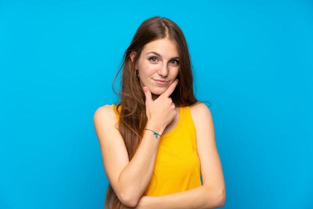 Jeune femme aux cheveux longs sur la pensée de mur bleu isolé Photo Premium