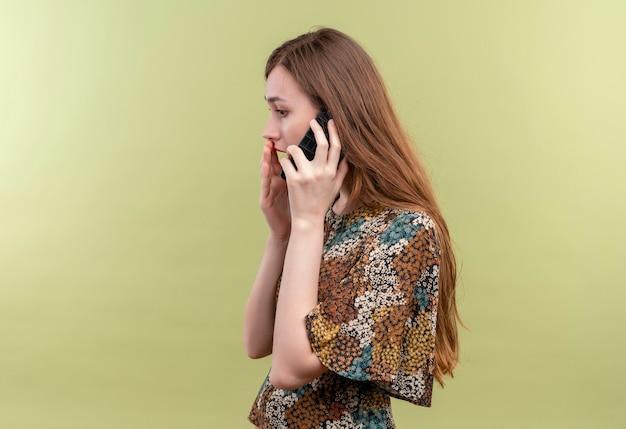 Jeune Femme Aux Cheveux Longs Portant Une Robe Colorée Surpris Et étonné De Parler Au Téléphone Mobile Debout Sur Un Mur Vert Photo gratuit