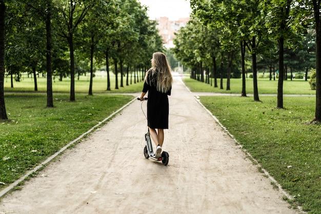 Jeune femme aux cheveux longs sur un scooter électrique. la fille sur le scooter électrique. Photo gratuit