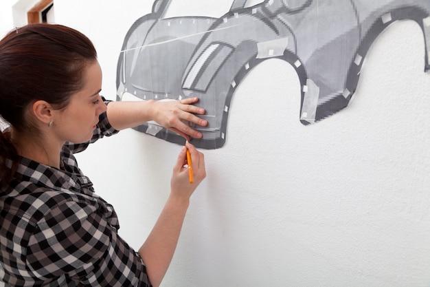 Une jeune femme aux cheveux noirs vêtue d'une chemise à carreaux dessine une grande voiture rouge dans la chambre du garçon accrochée au mur. Photo Premium
