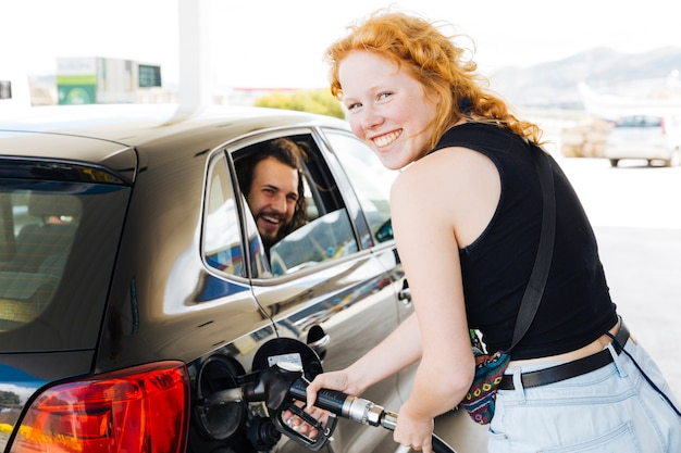 Jeune femme aux cheveux rouge remplissant le réservoir à la station d'essence Photo gratuit