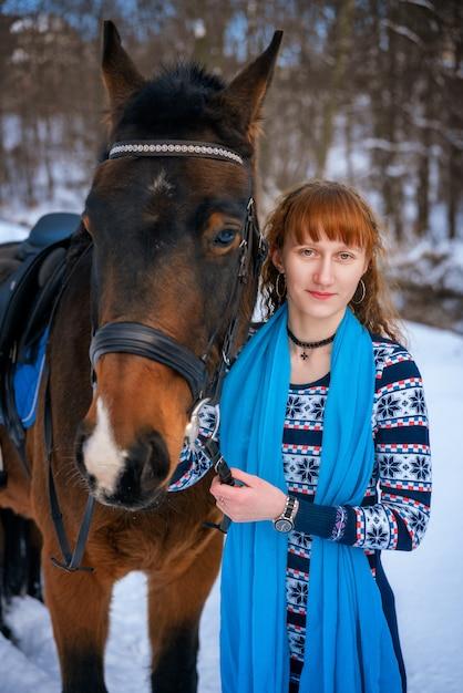 Jeune femme aux cheveux rouges sur un cheval en hiver Photo Premium