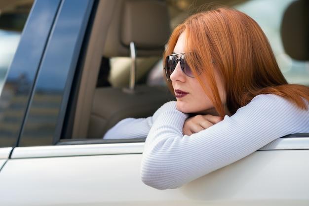Jeune Femme Aux Cheveux Rouges Et Lunettes De Soleil Voyageant En Voiture. Passager Regardant Par La Fenêtre Arrière D'un Taxi Dans Une Ville. Photo Premium