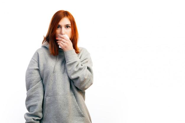 Une jeune femme aux cheveux roux vêtue d'un sweat-shirt gris est tombée malade d'un rhume Photo Premium