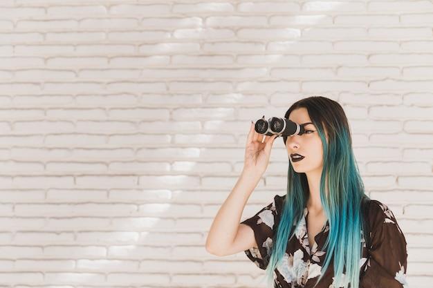 Jeune femme aux cheveux teints, regardant à travers des jumelles Photo gratuit