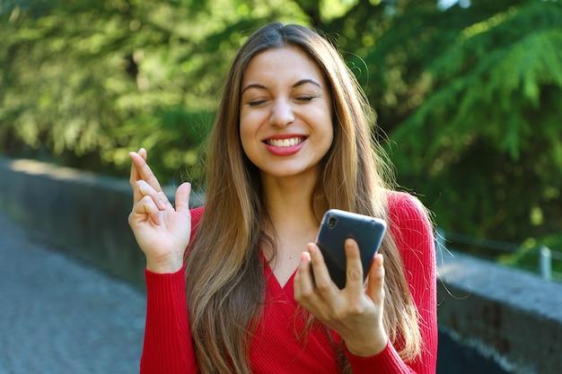 Jeune Femme Aux Doigts Croisés Et Téléphone Intelligent Souhaitant Le Meilleur à L'extérieur Photo Premium