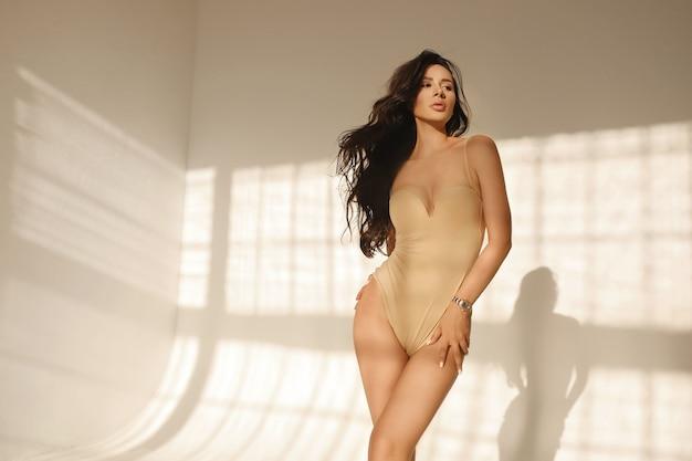 Une Jeune Femme Aux Lèvres Charnues Et Au Corps Parfait En Lingerie Body Beige Posant à L'intérieur Photo Premium