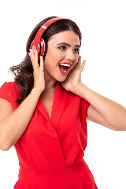 Une Jeune Femme Aux Lèvres Rouges écoute De La Musique Dans Les écouteurs Et Sourit Photo Premium