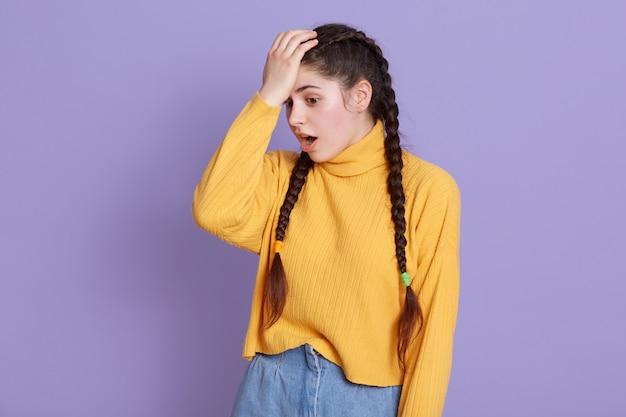 Jeune Femme Aux Longs Cheveux Noirs Et Nattes Debout Avec La Bouche Ouverte, Gardant La Main Sur Le Front Photo gratuit