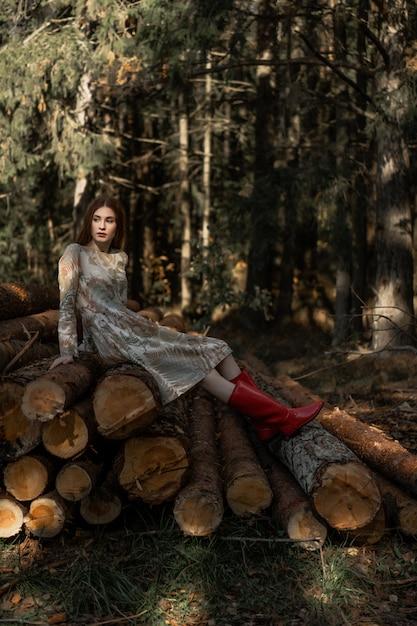 Jeune femme aux longs cheveux roux vêtue d'une robe en lin cueillant des champignons dans la forêt Photo gratuit